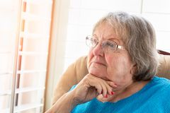 Contemplative Senior Woman Gazing Out of Her Window Royalty Free Stock Photo