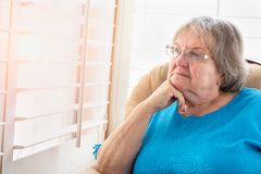 Contemplative Senior Woman Gazing Out of Her Window Stock Photo