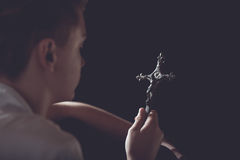 Contemplative Teenage Boy Holding Ornate Cross Royalty Free Stock Photography