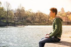 Contemplative teenage boy sitting beside river Stock Photo