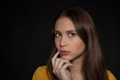 Contemplative thinking woman student at a black background - Stock Image Stock Photography