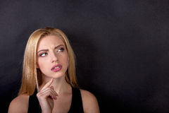Contemplative thinking woman student at a black background - Stock Image Stock Image