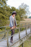 Contemplative trendy young woman on a footbridge. Contemplative trendy young woman on a rustic wooden footbridge standing leaning on the rail looking Royalty Free Stock Photo