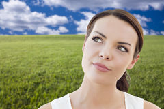 Contemplative Woman in Grass Field Looking Up and Over Stock Photo