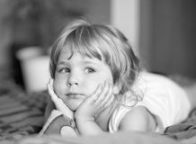 Contemplative young girl. Contemplative small girl lying and leaning on her hands Stock Photo