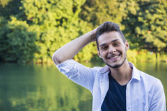 Contemplative young man sitting beside river Stock Photography