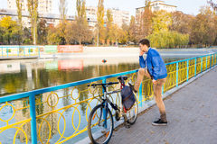 Contemplative young man. Standing staring into an urban canal or lake with his foot resting on his bicycle on a promenade Stock Photo