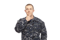 Contemplative young navy man with hand on chin. Contemplative young man in navy uniform with hand on chin against white background Royalty Free Stock Photo