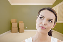 Contemplative Young Woman Daydreaming in Empty Room with Boxes. Attractive Daydreaming Young Woman in Empty Green Room with Boxes Royalty Free Stock Image