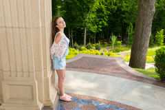 Contemplative young woman standing near wall in a park Stock Photo