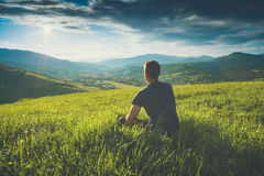 Contemplator. Instagram stylisation. Tourist sitting on a hill in a green grass and enjoy majestic sunset above carpathian mountain valley. Instagram stylisation Stock Photo