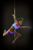 Contemporary active go-go dancer posing on pylon Stock Image