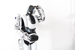 Contemporary affable creature of robotics. I have to serve people. Robot standing and putting one hand on head. Isolated and copy space Royalty Free Stock Photos