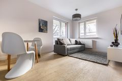 Contemporary apartment with beautiful chairs. Contemporary apartment with two beautiful chairs, dining table and small sofa royalty free stock photography