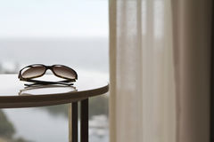 Contemporary apartment with sunglasses and view. Sunglasses on a table in a luxury hotel room or apartment with blurred view of the ocean behind Stock Photo