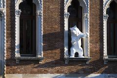Contemporary art: sculpture of a white bear standing in a window. At a canal in Venice, Italy 2017-08-22 stock photography