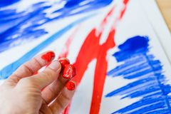 Contemporary art trend abstract finger painting. Contemporary art trend. Closeup of male hand with red acrylic paint on finger tips, over blurred abstract royalty free stock photo
