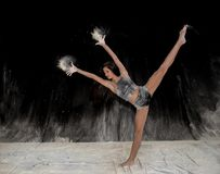 Contemporary ballet dancer dancing on the stage with flour. Expressive beautiful teenage female contemporary ballet dancing on stage with black background and royalty free stock photos