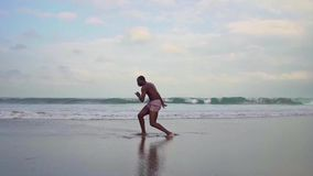 Contemporary ballet dancer performing at the beach. Gimbal shot on young attractive black African American man dancing by the sea stock video