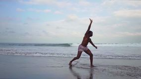 Contemporary ballet dancer performing at the beach. Gimbal shot on young attractive black African American man dancing by the sea. Contemporary ballet dancer stock video footage