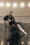Contemporary ballet dancer on a wooden chair on a repetition. Beautiful female contemporary ballet dancer in black wear posing on a wooden chair on a repetition royalty free stock photography
