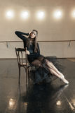 Contemporary ballet dancer on a wooden chair on a repetition. Beautiful female contemporary ballet dancer in black wear posing on a wooden chair on a repetition stock photos