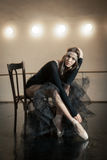 Contemporary ballet dancer on a wooden chair on a repetition. Beautiful female contemporary ballet dancer in black wear posing on a wooden chair on a repetition stock photo