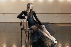 Contemporary ballet dancer on a wooden chair on a repetition. Beautiful female contemporary ballet dancer in black wear posing on a wooden chair on a repetition stock images