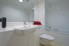 Contemporary bathroom. In white with large mirror over the wall stock image