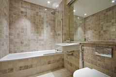 Contemporary bathroom with natural stone tiles. Modern bathroom with natural stone floor to ceiling tiles Stock Image