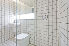 Contemporary bathroom with retro white tiled walls. Ceramic hand wash basin, toilet and large shower corner Stock Image
