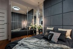 Contemporary bedroom with double bed. Contemporary and elegant bedroom with double bed and mirrored wardrobe stock photography