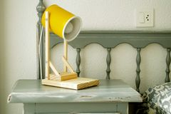 Contemporary bedside table with yellow lamp stock photo