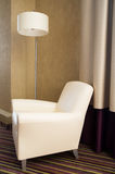 Contemporary beige comfortable armchair with lamp. Furniture Royalty Free Stock Photo