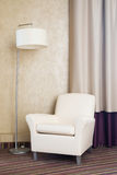 Contemporary beige comfortable armchair with lamp. Furniture Stock Photos