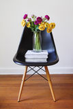 Contemporary black dining chair with yellow and purple flowers. Contemporary black dining chair with vase of yellow and purple flowers stock photography