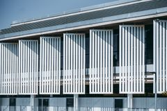Contemporary bright building facade. Frontal view of abstract white contemporary building facade with striped metal vertical blocks casting triangle shadows royalty free stock photo
