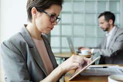 Contemporary Businesswoman in Co-Working Space. Portrait of business people working at separate tables in office co-working space, women  using digital tablet Stock Photo