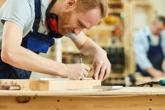 Contemporary Carpenter in Shop. Cropped portrait of contemporary carpenter working with wood standing at table in workshop, copy space royalty free stock photo