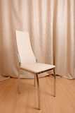 Contemporary chair standing in front of curtains background Stock Photo