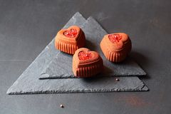 Contemporary Chocolate Mini Mousse Cake made in heart shape silicone mold. Covered with brick color velvet spray and decorated with blood orange caviar, on royalty free stock photography