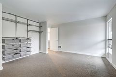 Contemporary condo home interior. Grey empty bedroom with freshly painted walls, open closet with storage system. Northwest, USA Stock Photos