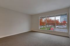 Contemporary condo home empty room. Contemporary condo home interior, grey empty room with window view. Northwest, USA Stock Image