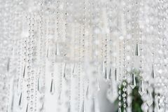 Contemporary crystal chandelier in room interior. Close up. The interior of a bright room of an apartment or a hotel Stock Photo
