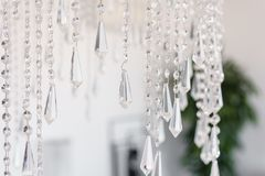 Contemporary crystal chandelier in room interior. Close up. The interior of a bright room of an apartment or a hotel Royalty Free Stock Images