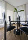 Contemporary dining area. Luxury dining table within an open plan living room with floor to ceiling windows Royalty Free Stock Photography