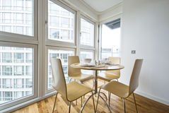 Contemporary dining area set up for four. Contemporary dining area with round wooden table, chairs, set up and floor to ceiling windows Royalty Free Stock Image