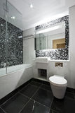 Contemporary en-suite bathroom in black and white. With white ceramic bath tub, wash basin and toilet with mosaic tiled walls and marble fragments Royalty Free Stock Photo