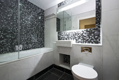 Contemporary en-suite bathroom in black and white. With white ceramic bath tub, wash basin and toilet with mosaic tiled walls and marble fragments Royalty Free Stock Photos