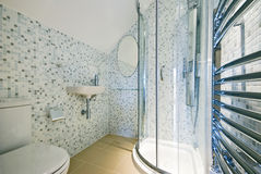 Contemporary en-suite bathroom with shower corner. White ceramic hand wash basin, toilet and mosaic tiled walls Stock Photo